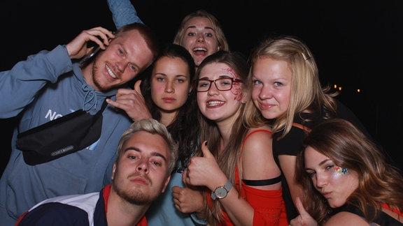 Gruppenbild von 7 lachenden jungen Menschen. 5 Männer und 2 Frauen.