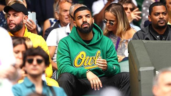 Drake sitzt in mitten von anderen Leuten auf einem Stuhl im Stadion.