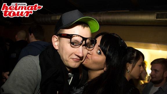Ein küssendes Paar guckt direkt in die Kamera. Dem Mann ist die Brille hoch gerutscht.