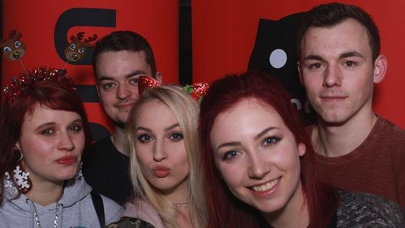 Fünf Partygäste posieren vor der SPUTNIK Wand