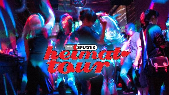 Tanzenden Menschen im Club in blaues Licht getaucht.