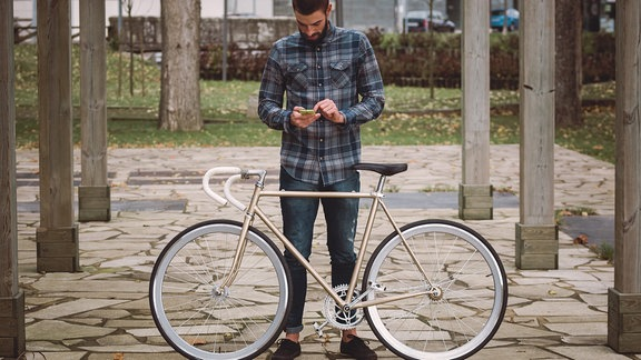Ein junger Mann mit Bart im Holzfäller-Hemd schaut aufs Smartphone. Vor ihm steht ein Rennrad mit goldenem Rahmen und weißem Lenker.