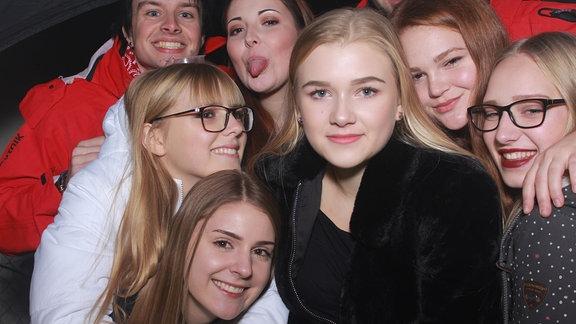 Vier junge Frauen und ein Mann lächeln in die Kamera.