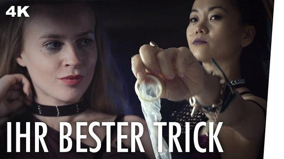 Zwei Frauen, eine hält ein benutztes Kondom in der Hand.