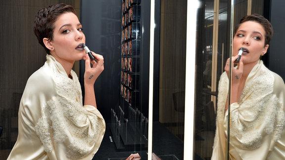 Halsey sitzt vor einem riesigen Spiegel und zieht sich die Lippen mit einem dunklen Lippenstift nach. Sie trägt einen cremefarbenen, perlenbesetzten Satin-Morgenmantel.