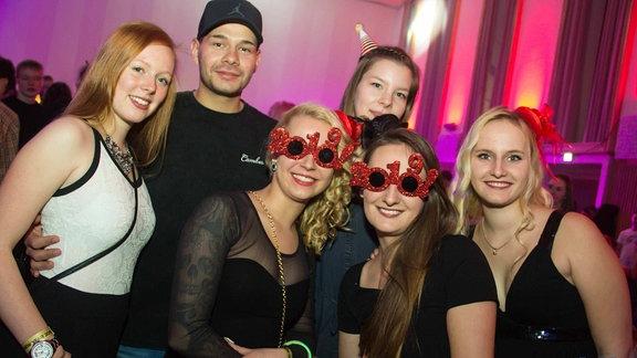 Ein Gruppe junger Menschen. Zwei Mädchen in der Mitte tragen rote 2019-Glitzerbrillen.