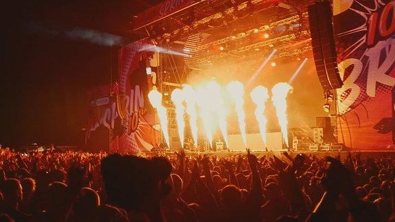 Feiernde Menschen stehen vor der SPUTNIK SPRINGBREAK Bühne, nachts, Pyrotechnik.