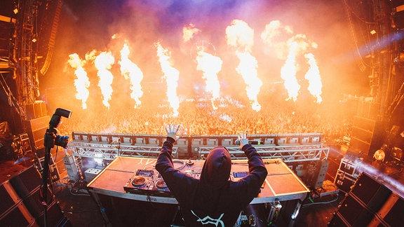 Der Künstler Alan Walker auf der Bühne und in der Menge sind große Flammenwerfer zu sehen.