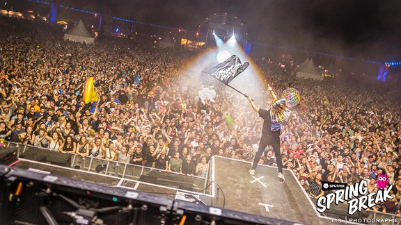 Die Bühne im Vordergrund, feiernde Menschenmassen im Hintergrund