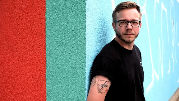 DJ Filburt steht angelehnt an eine bunte Wand. Er trägt eine Brille, schwarzes einfaches T-Shirt, blonde Haare. Auf dem rechten Oberarm hat er ein Tattoo.