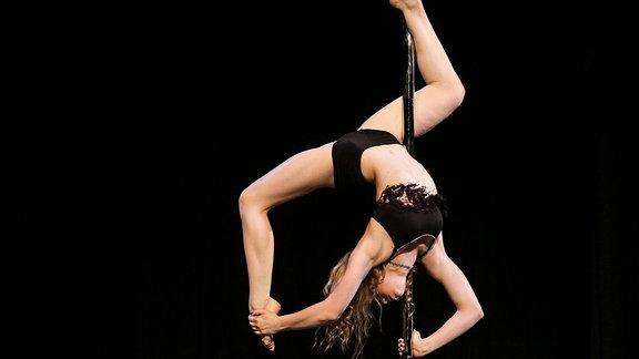Frau macht Poledance