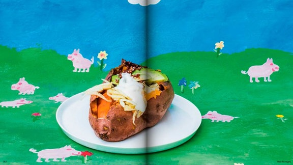 Eine gefüllte Süßkartoffel vor einem selbstgemalten Bild mit blauem Himmel, Wieso, kleinen rosa Schweinchen und weißen Bauschewolken.