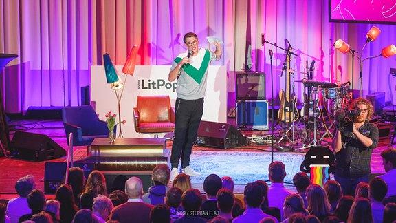 Ein Poetry-Slammer auf der Bühne im Festsaal im neuen Rathaus in Leipzig. Auf der Bühne Instrumente, gemütliche Sessel, ein Couchtisch aus übderdimensional großen Büchern. Vor der Bühne viele Zuhörer und ein Kameramann, der das Publikum filmt.