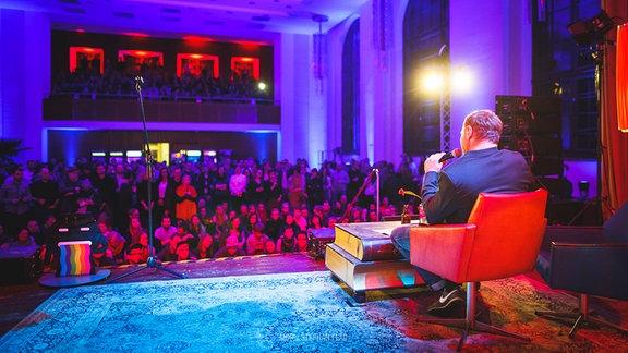 Ein Autor auf der Bühne im Festsaal im neuen Rathaus in Leipzig.