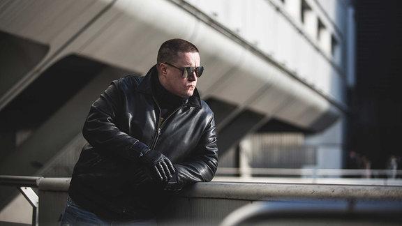 Morlockk Dilemma Rapper in Lederjacke und Sonnenbrille