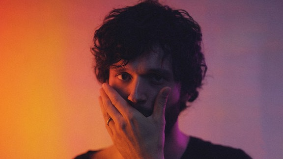 Der Musiker Apparat hat eine Hand vorm Mund und steht vor eine rot-blauen Hintergrund.