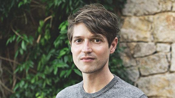 Autor Benedict Wells vor einer überwucherten Wand