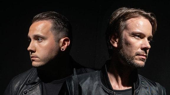 Die beiden DJs von M22 gucken beide in die jeweils gegenüberliegende Richtung, links und rechts an der Kamera vorbei.