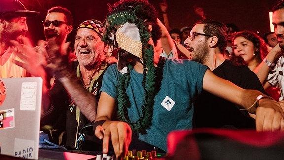DJ Guedra Guedra legt im Boiler Room auf einer Party auf. Sein Gesich von Schmuck verdeckt.
