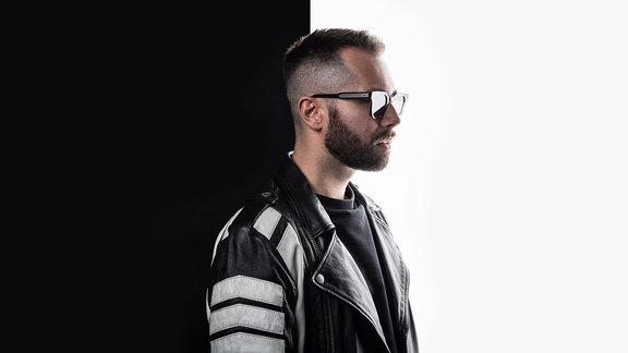 David Puentez steht seitlich und trägt eine Sonnenbrille. Das Bild ist in gleißendem Licht auf der einen Seite, auf der anderen Seite ist es dunkelschwarz.