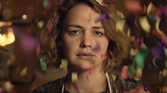 """Schauspielerin Luise Heyer in einer Filmszene aus """"Einmal bitte alles"""". Sie steht im Konfettiregen und schaut in die Kamera."""