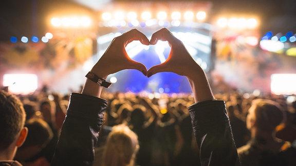 Jemand formt ein Herz mit seinen Händen vor einer vollen Festivalbühne