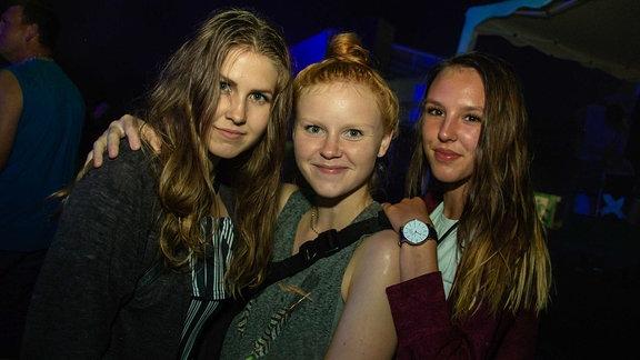 Drei junge, weibliche Partygäste lächeln in die Kamera.