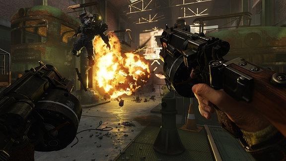 Zwei Hände mit schweren Waffen, im Hintergrund eine Explosion