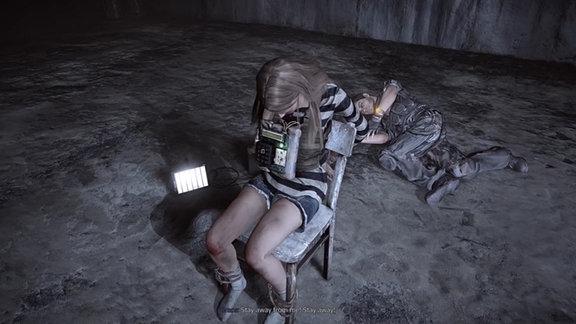 Eine Szene aus dem Computerspiel Get Even. Eine Frau sitzt auf einem Stuhl gefesselt und hat eine Bombe um den Hals. Hinter ihr liegt ein Mann. Auf dem Boden ist ein Laptop