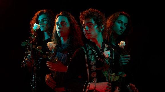 Die Band Greta van Fleet in sehr dunklen Farben. Alle vier Bandmitglieder halten eine Rose in der Hand.