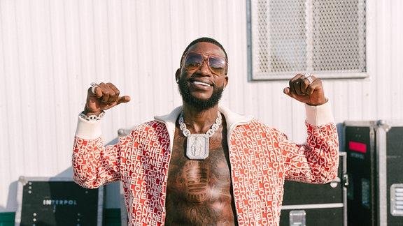 Gucci Mane post mit offener Jacke, fetten Tatts und dicken Muskeln.