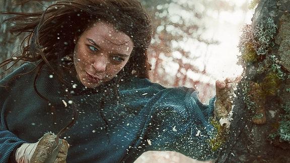 Hanna steht im Wald und es schneit.