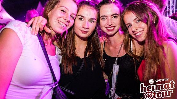 Vier Partymäuse partymäßig in die Kamera grinsend.