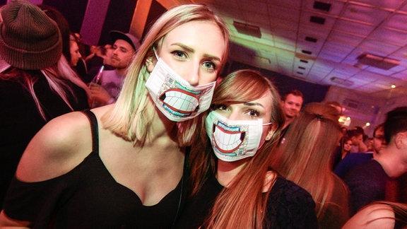 Zwei junge Frauen mit Housekasper-Mundschutz stehen in der feiernden Menge.