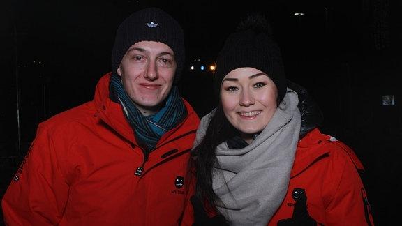 Zwei Eisbahnbesucher in roten Winterjacken.