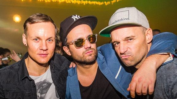 Drei junge Männer in Partystimmung.