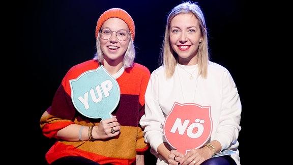 Stefanie Heinzmann und Sissy Metzschke sitzen auf zwei Hockern vor einem schwarzen Hintergrund.