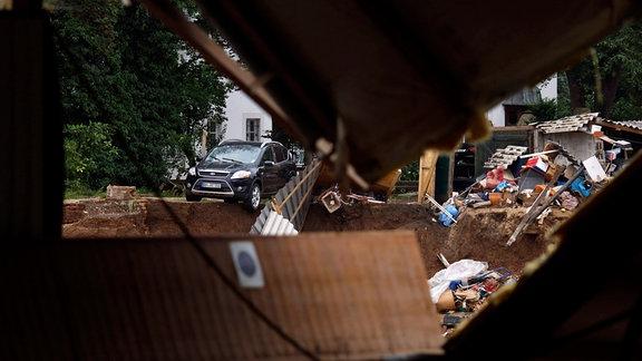 In Erftstadt-Blessem (NRW) sind Häuser massiv unterspült worden und einige eingestürzt oder in eine nahe Kiesgrube gestürzt. An deren Rand hatte sich wasserbedingt ein Krater gebildet, der umliegende Felder immer weiter in die Kiesgrube rutschen ließ. Es werden etliche Personen vermisst. Noch mehr Häuser drohen abzurutschen. Der Katastrophenschutz ist vor Ort. Im Bild herabgestürzte Autos in Blessem.