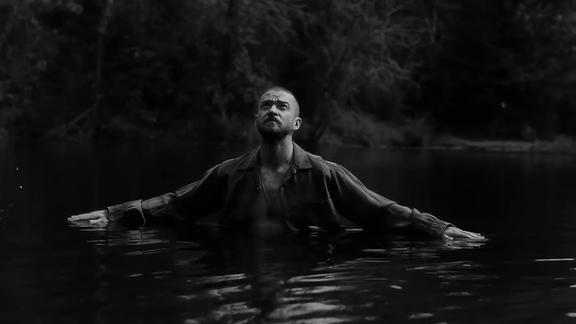 Justin Timberlake mit ausgebreiteten Armen in einem See