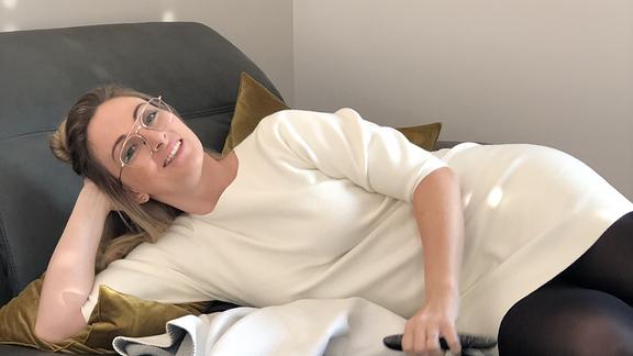 Kathrin Watzke, eine SPUTNIK-Redakteurin, liegt mit der Fernbedienung auf der Couch