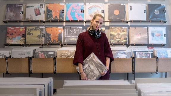 Labelbossin Lina steht in einem Plattenladen und halt ein Vinylalbum in den Händen. Sie trägt die blonden Haare zurückgebunden und hat große Kopfhörer um den Hals baumeln. Sie trägt einen oversized Pulli.