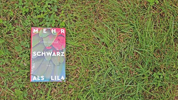 """Das Buch """"Mehr Schwarz als Lila"""" liegt auf einer Wiese"""
