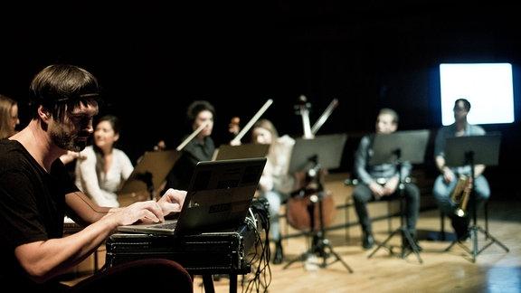 The Micronaut sitzt mit mehreren Orchestermusikern auf einer Bühne.
