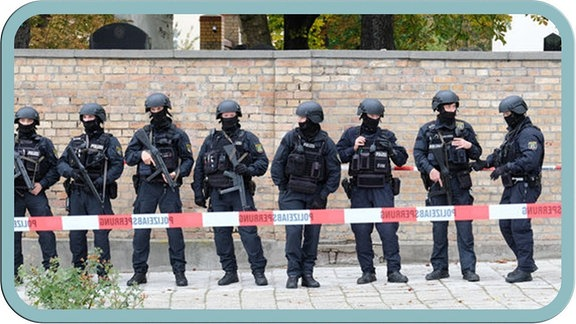 Polizisten in Vollschutz vor der jüdischen Friedhosmauer in Halle