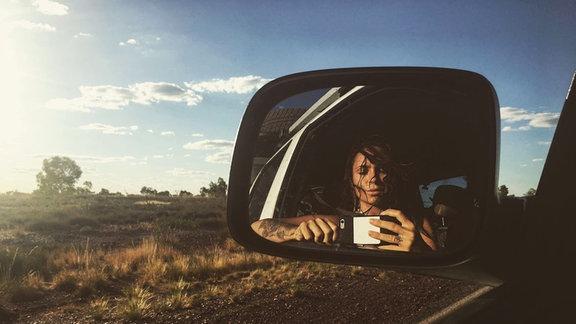 Nic Jordan schießt ein Selfie von sich im Seitenspiegel.