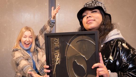 Zoe Wees hält stolz ihren New Music Award als Durchstarterin des Jahres in den Händen, Sissy von MDR SPUTNIK ist hyped im Hintergrund.