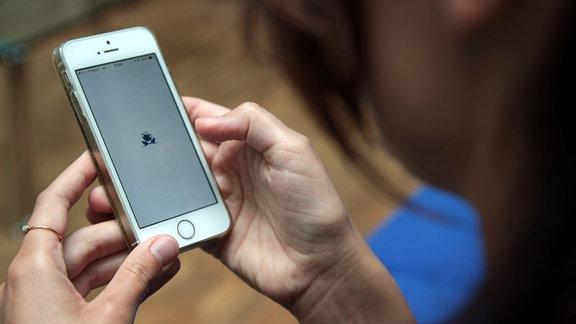 Blick über die Schulter einer jungen Frau auf ein Handy. Auf dem Display ist das Logo der App Once erkennbar.