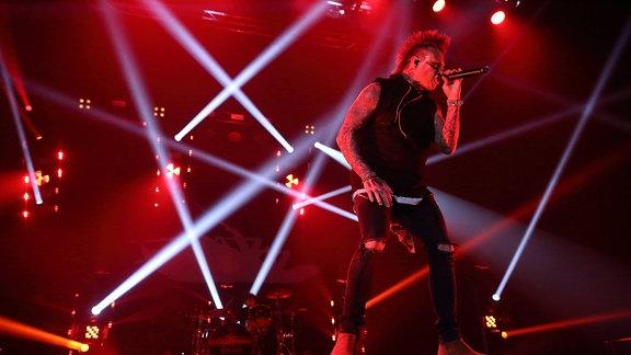 Papa Roach live in rotem Scheinwerferlicht.