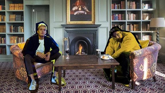 Felix Brummer und Steffen Israel wurden als Collage in ein Foto eines Schlosswohnzimmers heineingephotoshopt. Beide sitzen auf bunten Sesseln, hinter ihnen lodert ein Feuer in einem schwarzen Kamin, über dem ein großes Gemälde hängt. im Hintergrund sind viele Bücher in Regalen und eine alte Stehlampe zu sehen.