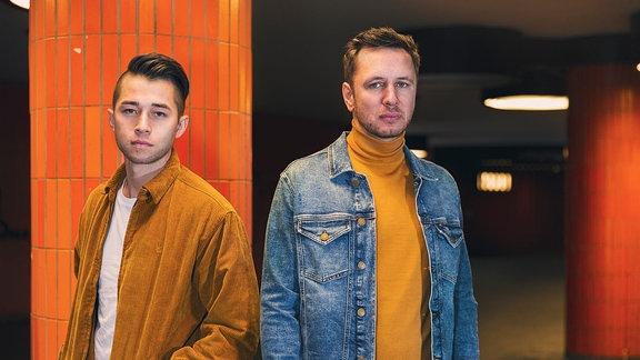 Die beiden von VIZE chillen in Retro-Kleidung einer U-Bahn-Station.